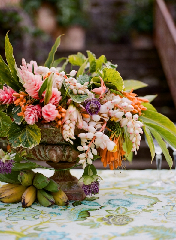 a lush floral centerpiece plus bananas is suitable for a tropical or beach wedding