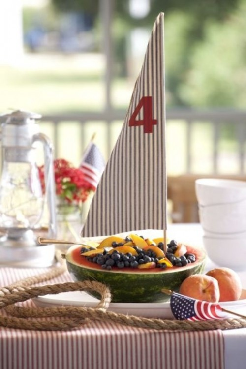 an edible wedding centerpiece with a watermelon and berries plus a sail looks like a boat, and it's very original