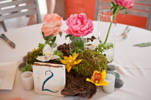 a tropical beach wedding centerpiece with driftwood, tropical blooms, a table number and candles