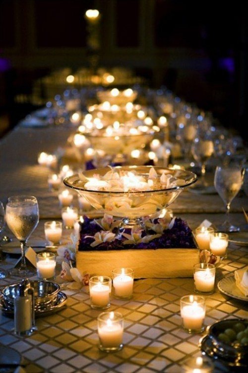 a clear bowl with floating candles and blooms plus candles all around