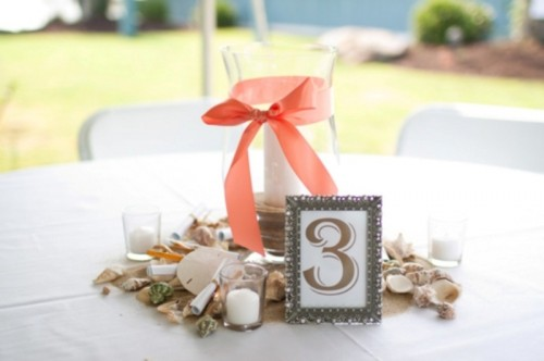 a beach wedding centerpiece with seashells, candles and a large candle holder with a ribbon bow