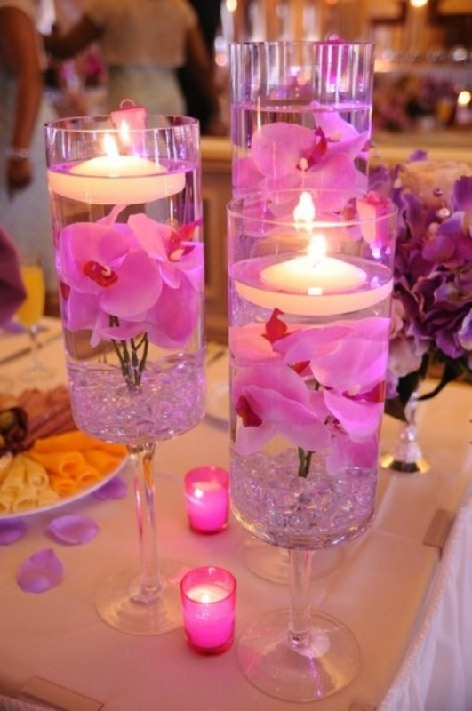 glasses with bright purple petals and floating candles and candles around for a tropical beach wedding