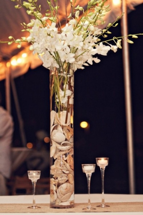 a tall clear glass vase with seashells, white blooms and candles all around