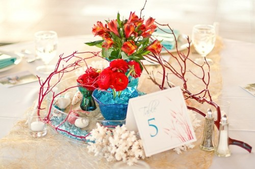 a beach wedding centerpiece with corals, seashells, branches and bright blooms in blue vases