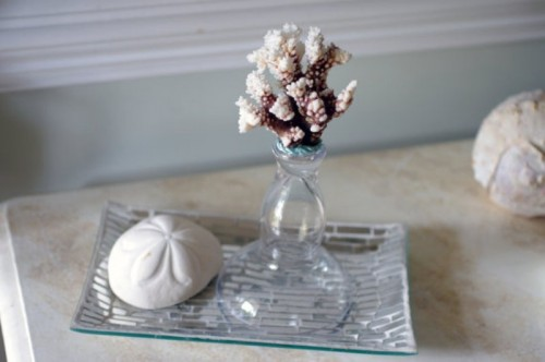 a silver tray with a starfish print, a vase with a piece of coral is a simple and casual idea