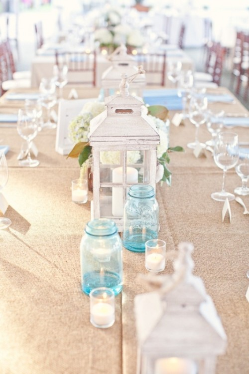 a white wooden candle lantern, blue jars with candles, candles in simple glass candle holders