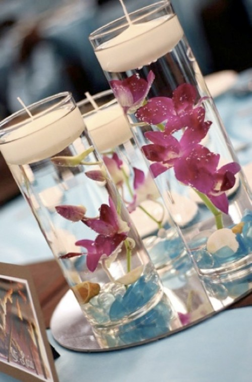 a mirror with tall glasses and purple orchids plus floating candles is a proper idea for a tropical beach wedding