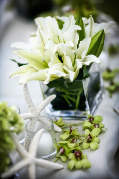 a clear vase with white lilies, green orchids and a starfish for a cute beachy wedding centerpiece