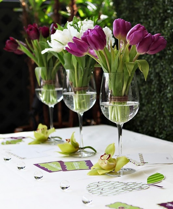 glasses with white and purple tulips and green orchids on the table for a tropical feel