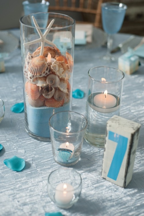 a clear vase with blue sand, seashells, starfish, clear glasses with candles for a beach-like centerpiece
