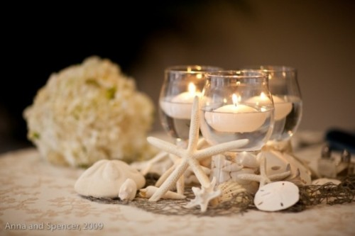 a beachy centerpiece with seashells, starfish and floating candles in clear glasses