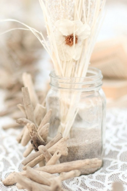 a jar with sand, dried grasses and driftwood is a simple beach centerpiece idea
