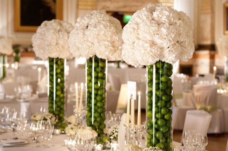 tall clear vases filled with green apples plus white hydrangeas is a creative wedding centerpiece idea