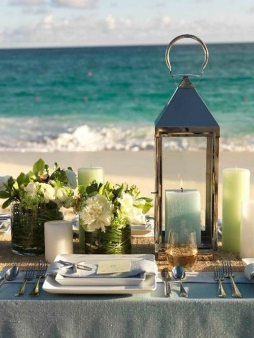 a candle lantern, green and blue candles, green and white floral arrangements in wrapped vases