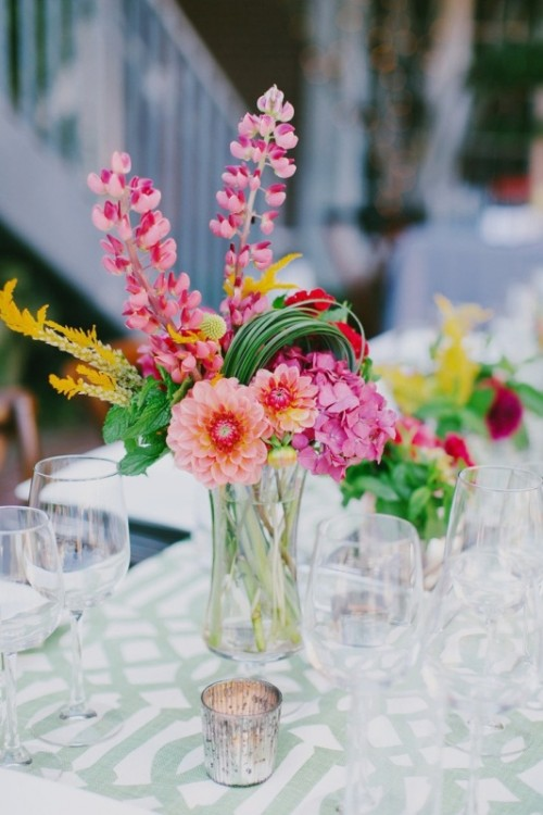 a clear vase with bright and colorful blooms plus greenery is a very fun idea for a tropical wedding