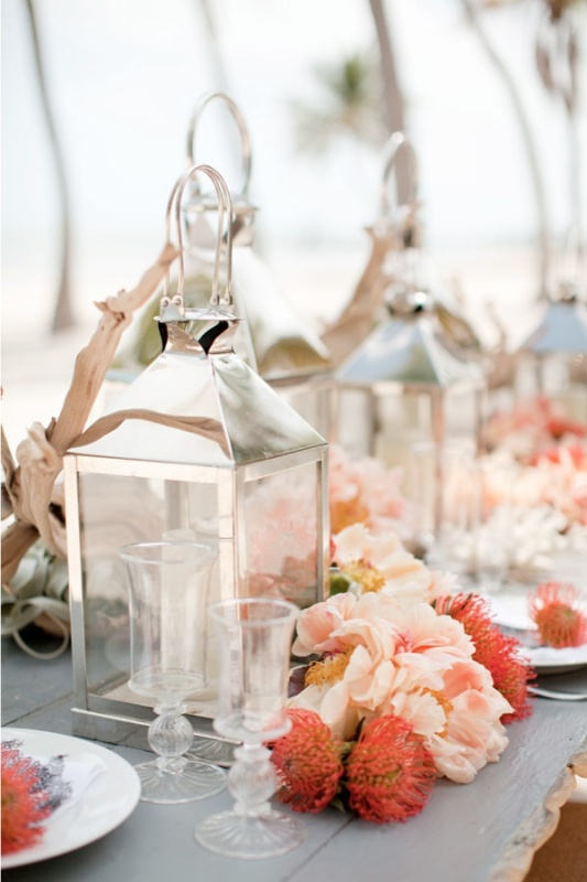 candle lanterns, driftwood and a bright floral garland with pincushion proteas and pink peonies