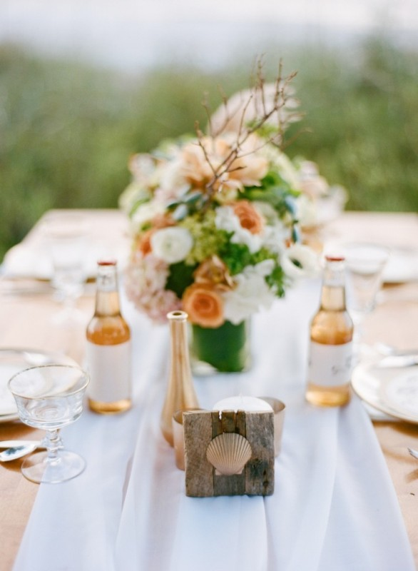 a peachy, white and green floral wedding centerpiece plus a pallet sign with a seashell