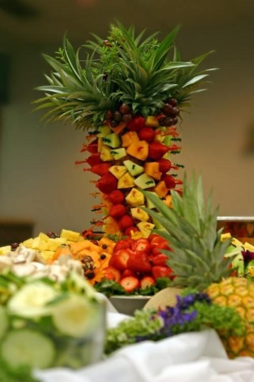 an edible tropical wedding centerpiece composed of tropical fruits creating a tower