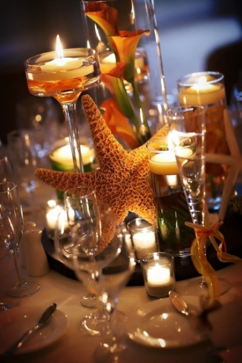 a tropical beach wedding centerpiece with a mirror, a starfish, candles and peachy callas