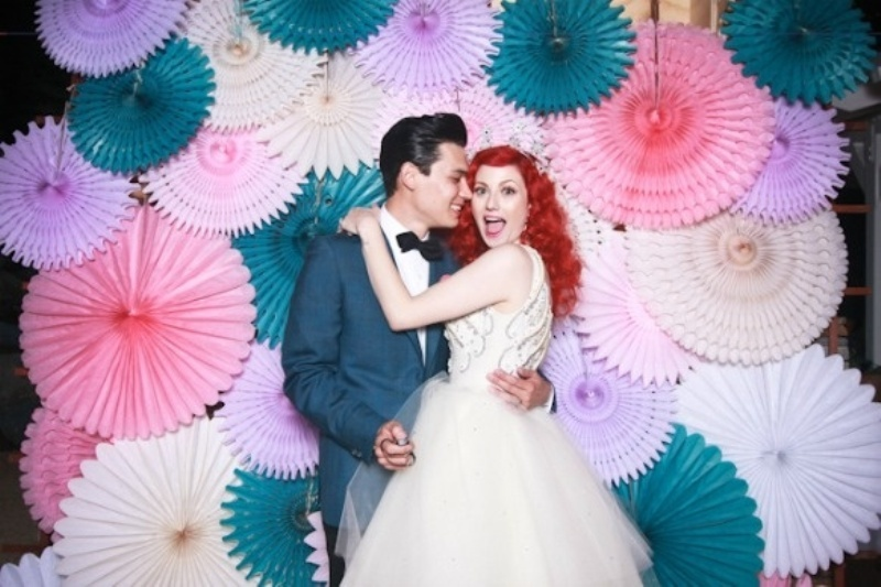 a lot of colorful paper fans on the wall are an amazing and bright wedding backdrop that cheers up the space