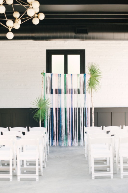 a simple wedding backdrop of colorful ribbons and some large palm leaves is a fast to DIY idea