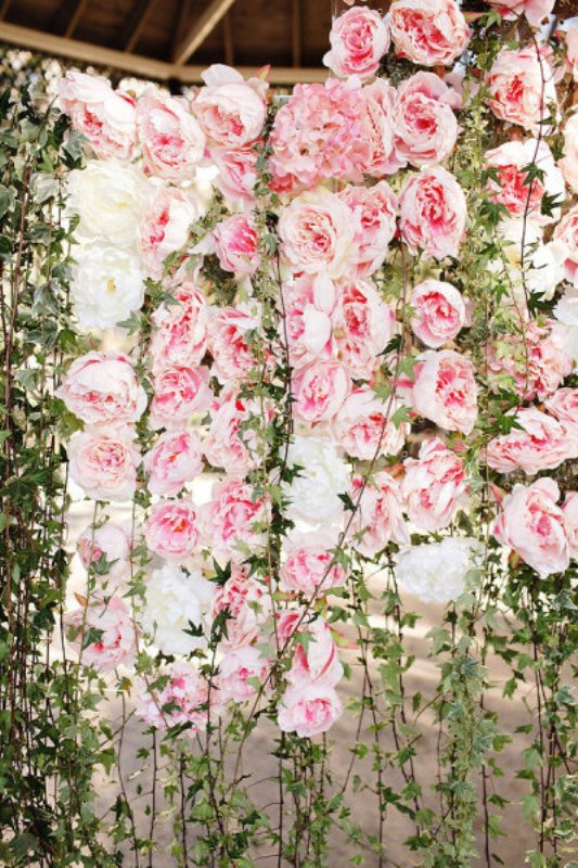 a fantastic wedding backdrop made of fresh foliage and pink paper peonies that look natural and perfectly imitate fresh blooms and greenery