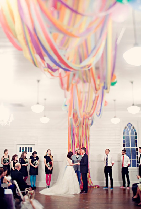 a colorful ribbon wedding backdrop that goes up to the ceiling and creates an installation there is a unique idea