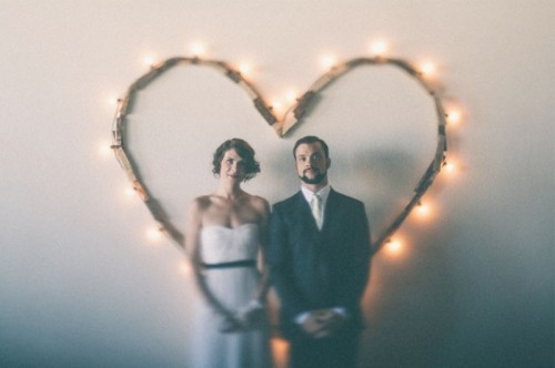 a simple and casual heart wedding backdrop made of reclaimed wood and lights can be easily DIYed by you yourself