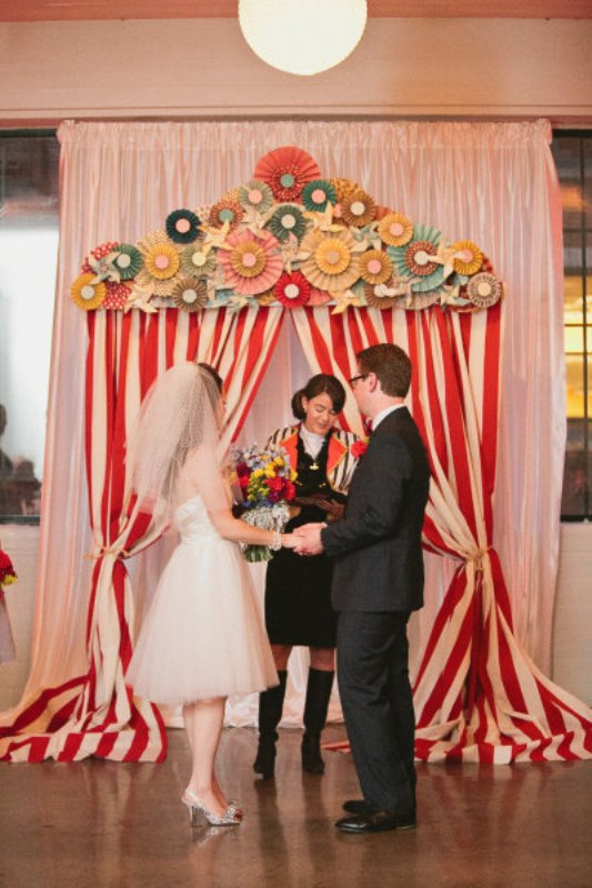 a colorful retro wedding backdrop imitating a tent, with striped curtains and colorful paper fans is a bright and fun idea