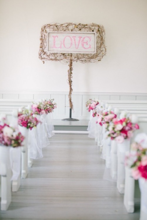 a simple wedding backdrop idea with a sign with vines and pink blooms accentuating the benches is a simple and cute option