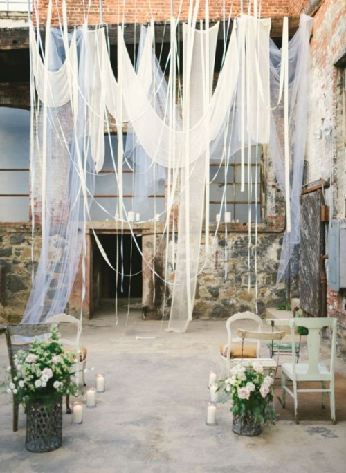 a dreamy wedding backdrop of white flowy and airy fabric hanging down asymmetrically and in various ways