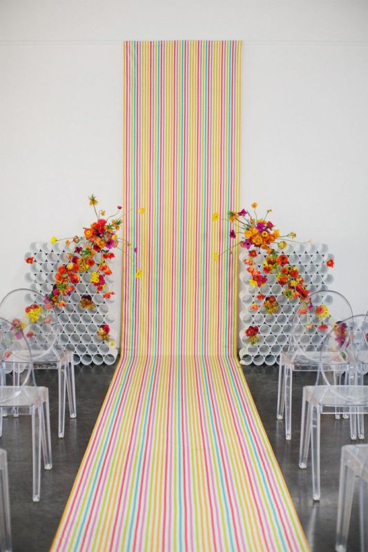 a chic and bright wedding backdrop of colorul striped wallpaper and PVC pipe installations with some colorful blooms is a bold idea
