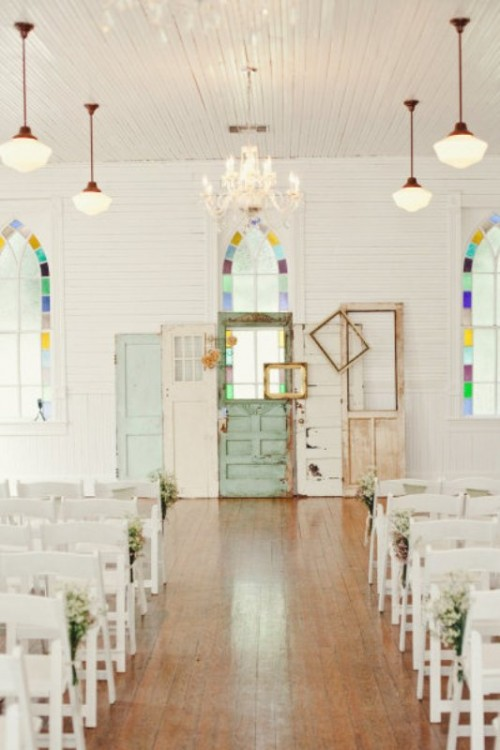 a vintage wedding backdrop composed of several shabby chic doors and frames in different colors is a very relaxed idea