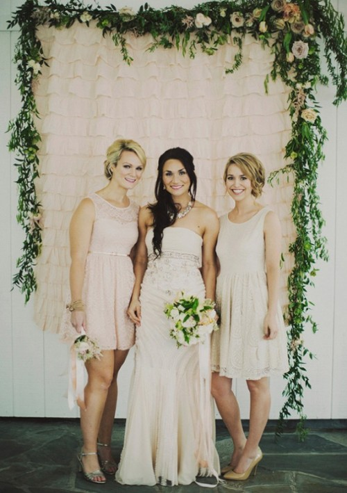 a chic and romantic wedding backdrop of blush fabric ruffles and a greenery garland with blush roses over it