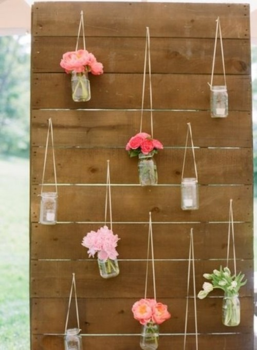 a rustic wedding backdrop with candle lanterns and bright floral arrangements in jars is a cool and cozy idea
