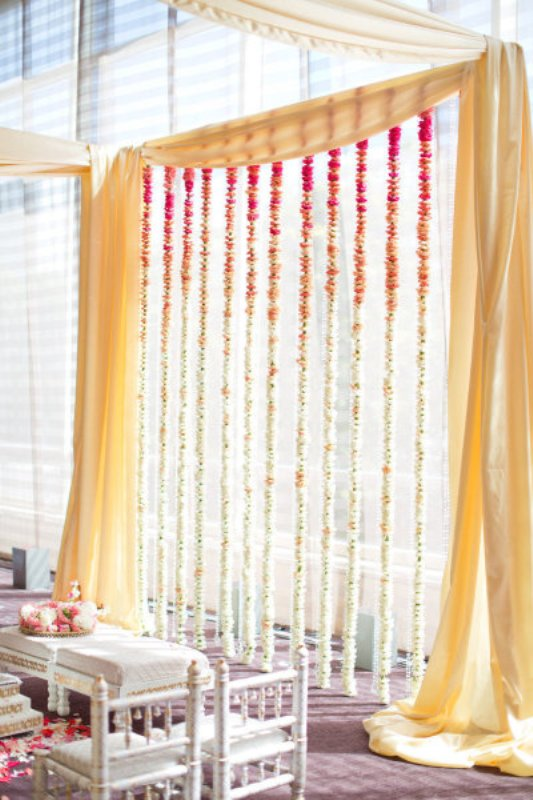 a gorgeous wedding backdrop with yellow curtains and bright ombre floral garlands to incorporate a hot color trend