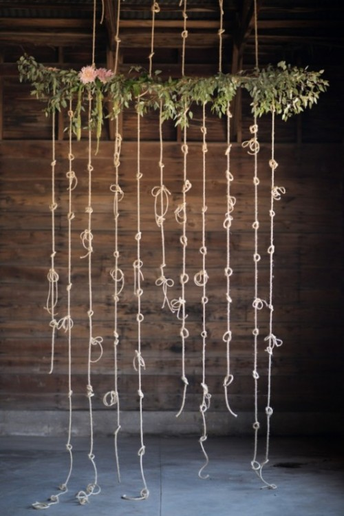 a fun wedding backdrop of greenery, some blooms and some ropes with knots to tie the knot in reality