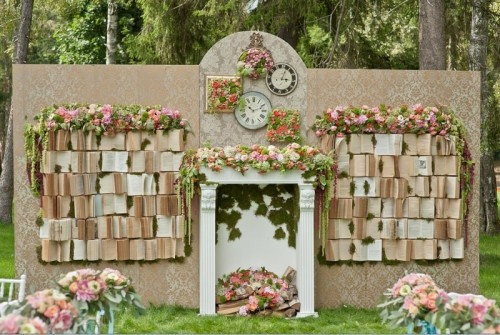 a whimsical wedding backdrop with vintage books, blooms, greenery, a fake fireplace and clocks is a beautiful idea for a vintage tea party wedding