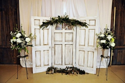 a vintage door and greenery wedding backdrop plus greenery and white florals on stands is a very cozy and cute idea