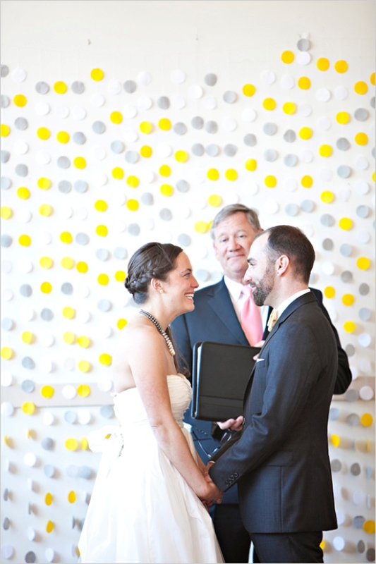 a bright modern wedding backdrop made of yellow and grey large polka dots attached right to the wall   simple and cute