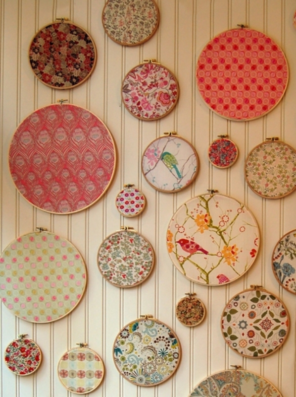 a wedding backdrop made of several embroidery hoops with bright pritned fabric is a cool and fun idea