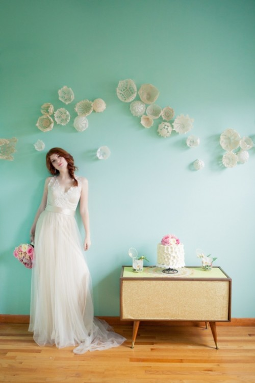 a pastel green wall with doily cups is amazing for a vintage-inspired and romantic wedding
