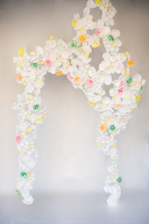 a wedding arch made of white, green, yellow and red paper flowers and featuring a creative shape