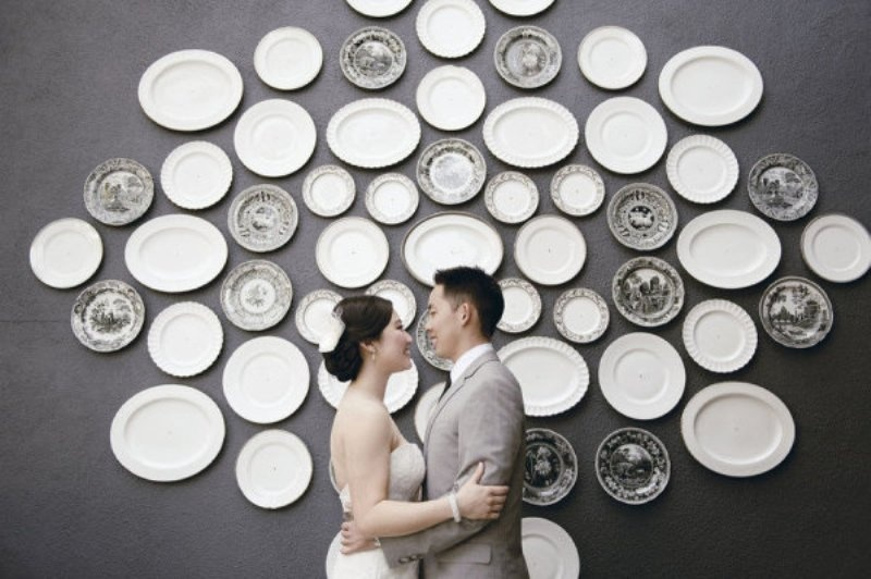 a wedding backdrop made of vintage plates in grey and white and with various patterns is a very chic idea