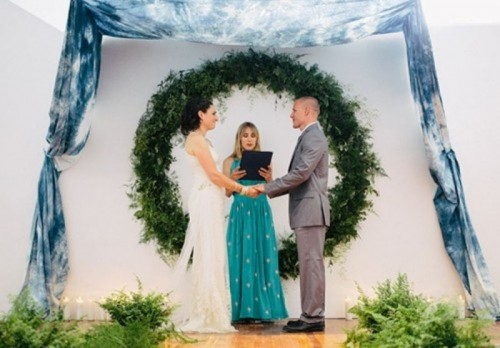 a round greenery wedding arch plus some tie dye blue fabric over will bring an outdoor feel indoors and will accent the couple