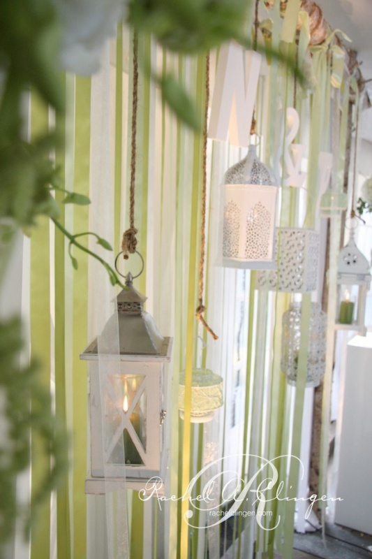 an indoor wedding backdrop made of colorful strips hanging down plus some candle lanterns is a timeless idea with light to highlight the couple