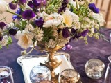 a purple tablecloth and a lush floral centerpiece with purple touches