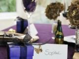 a purple tablecloth, purple petals and purple favor boxes