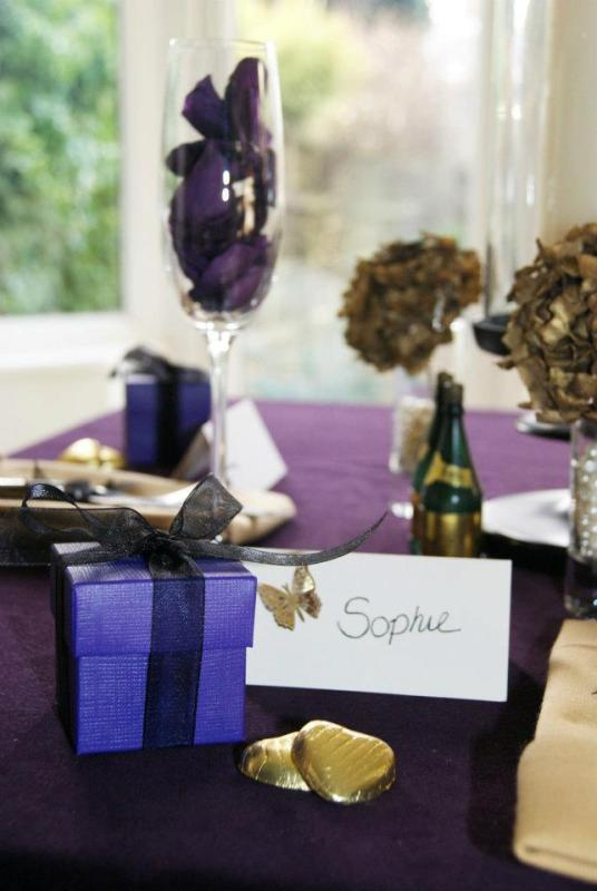 a purple tablecloth, purple petals and purple favor boxes