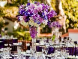 a bright purple tablecloth and a lush bright purple floral centerpiece make up a bold combo